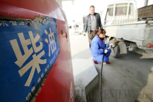 FUEL CHARGE: A staff member of a privately-owned gas station in Shandong Province refuels a truck.