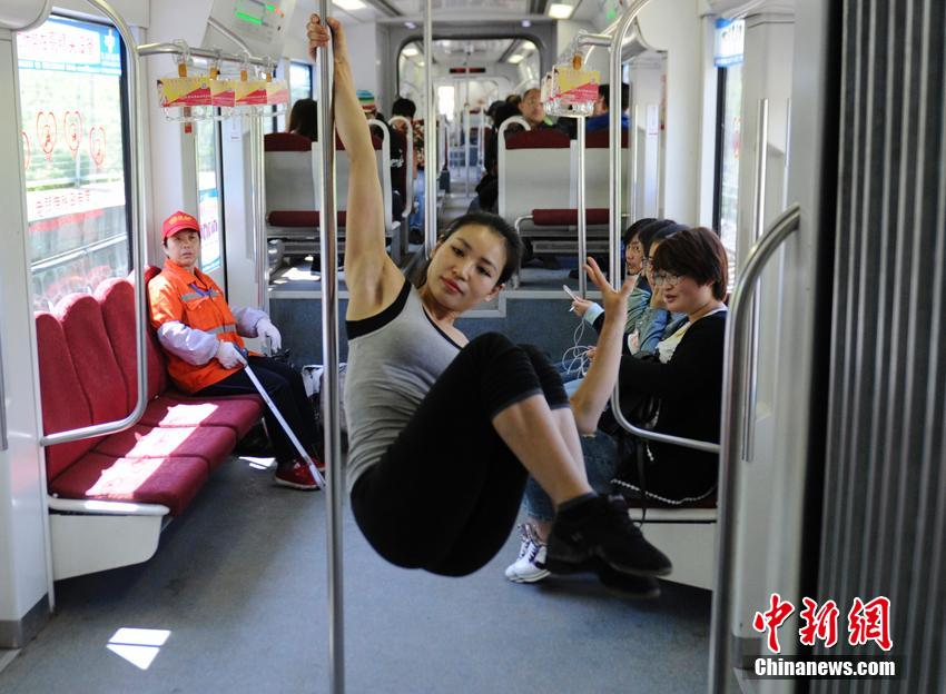 French, Chinese beauties pole dance on train to promote health