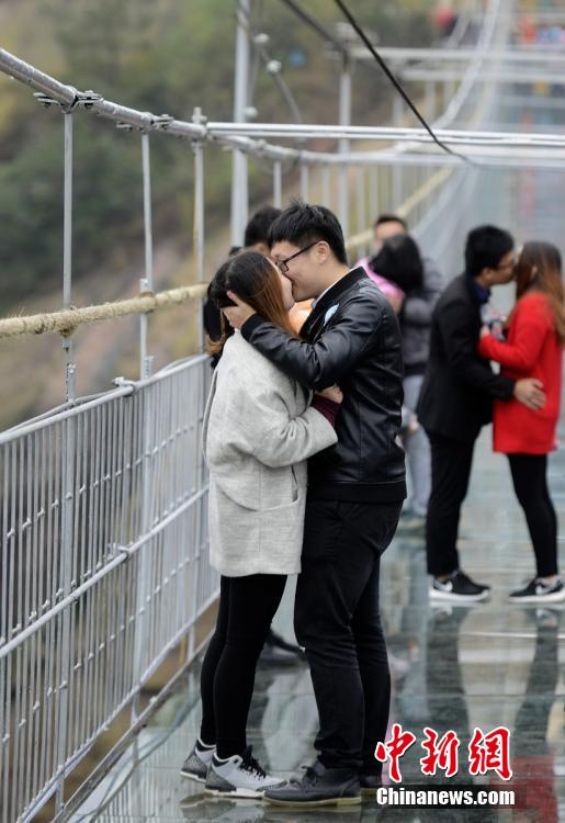 Couples kiss on glass bridge to celebrate not being single