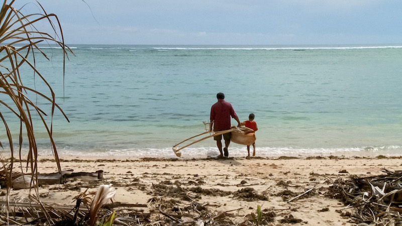 Patrick Malaki and son take their newly crafted boat out into the waters of the South Pacific