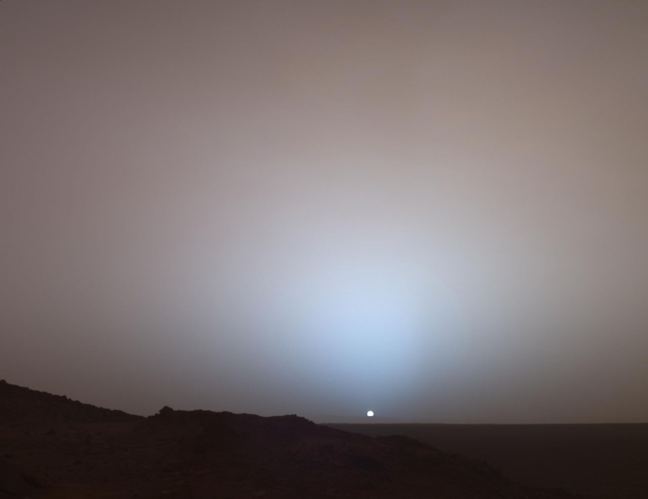 Mars Exploration Rover Spirit captures a stunning view as the sun sinks below the rim of the Gusev crater on Mars on May 19, 2005.