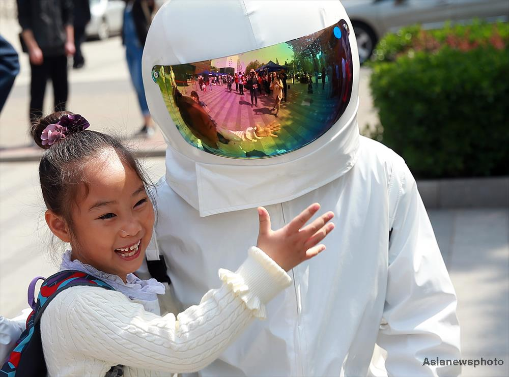 A schoolgirl hugs an astronaut at Beihang University in Beijing on China's first Space Day, April 24, 2016.
