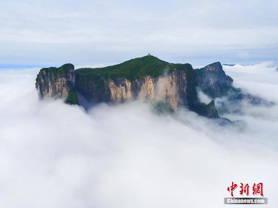 Heavy clouds blanket and roll around a cliff's peak in Hunan Province's Zhangjiajie National Forest Park on June 29.