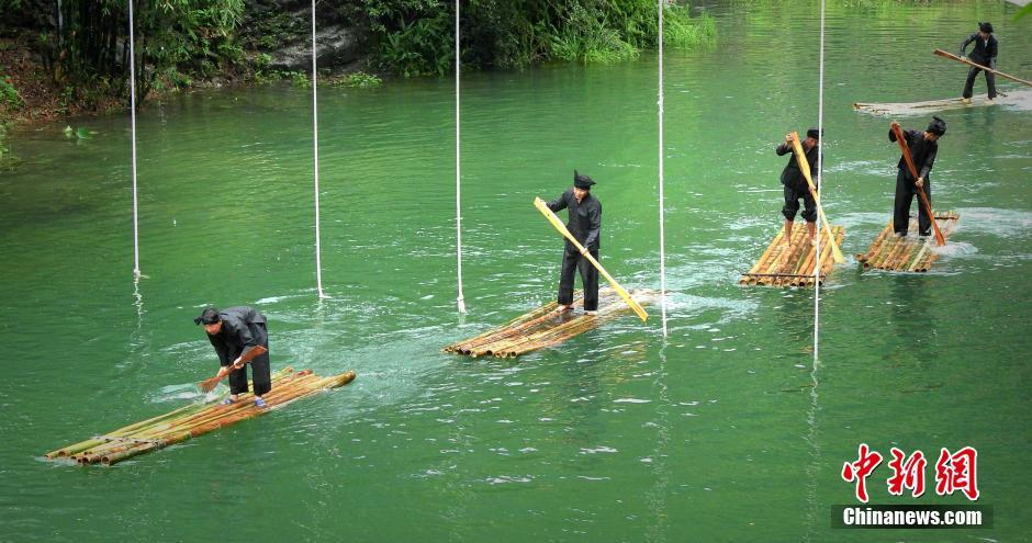 """Rafters participating in the """"Zhuang Triathlon"""" (rafts, swimming, climbing rope) in celebration of God of Water."""