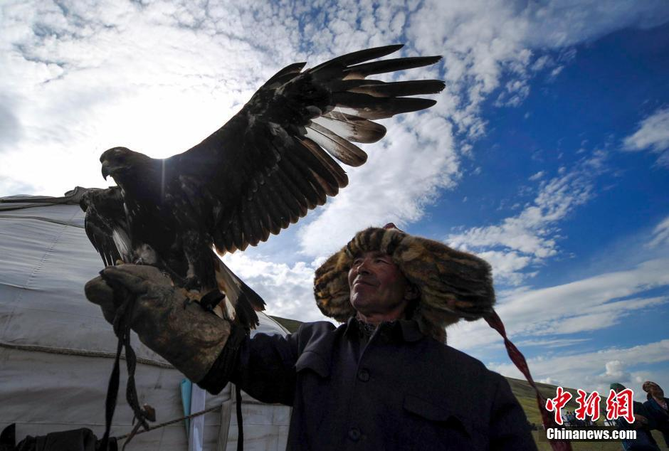 A Kazakh eagle hunter proudly displays his tamed bird of prey.