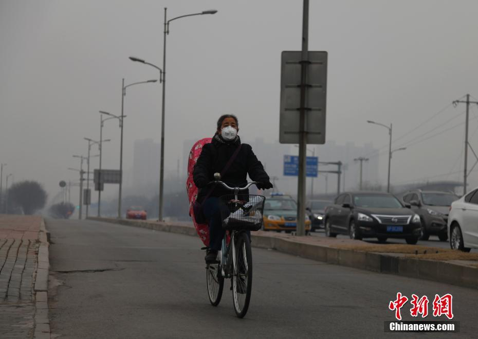 A masked woman cycles in Beijing on Monday, December 12, 2016.