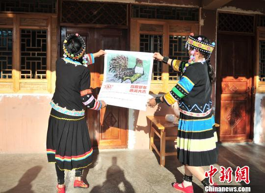 Two girls erect a New Year painting on the wall of their house in Pu'er, Yunnan Province.