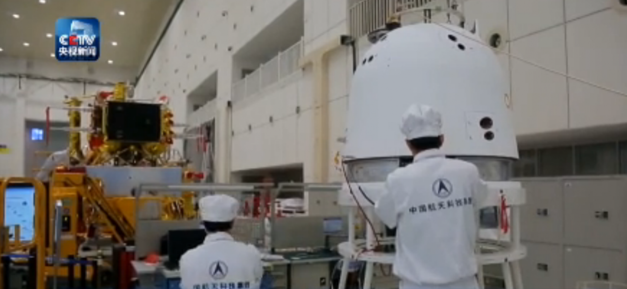 Scientists working on China's Chang'e-5 reentry vehicle, right, with lander and ascent vehicles in the background.