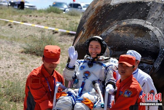 Liu Yang, China's first woman in space, in front of the charred Shenzhou-9 return capsule after spending two weeks aboard Tiangong-1.