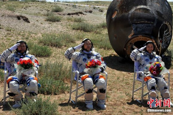 The crew of the 2012 Shenzhou-9 mission salute, safely back on Earth on June 29, 2012.