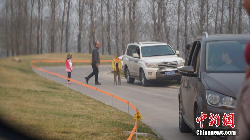 A man and two children get out of their car and walk on the road on a safari-style tour in the Beijing Wildlife Park, March 19, 2017.