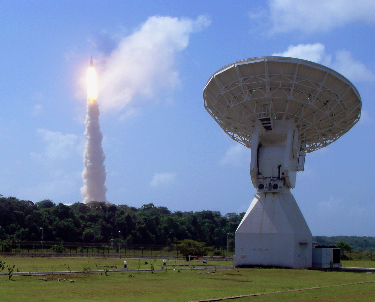The Ariane 5 V188 launcher carrying Herschel and Planck rises above ESA's 15 m-diameter tracking dish at Kourou, French Guiana, on 14 May 2009.