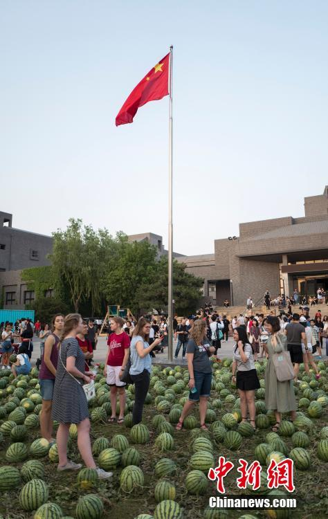 Visitors and students on the lawn covered by watermelons in China Central Academy of Fine Arts on Thursday.