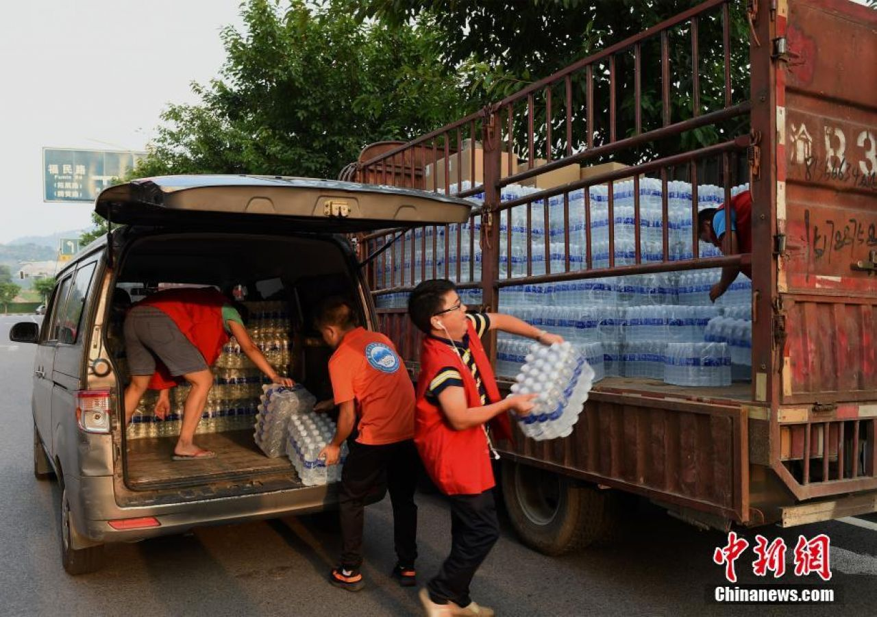 Volunteers carrying water to a truck heading into the disaster area.