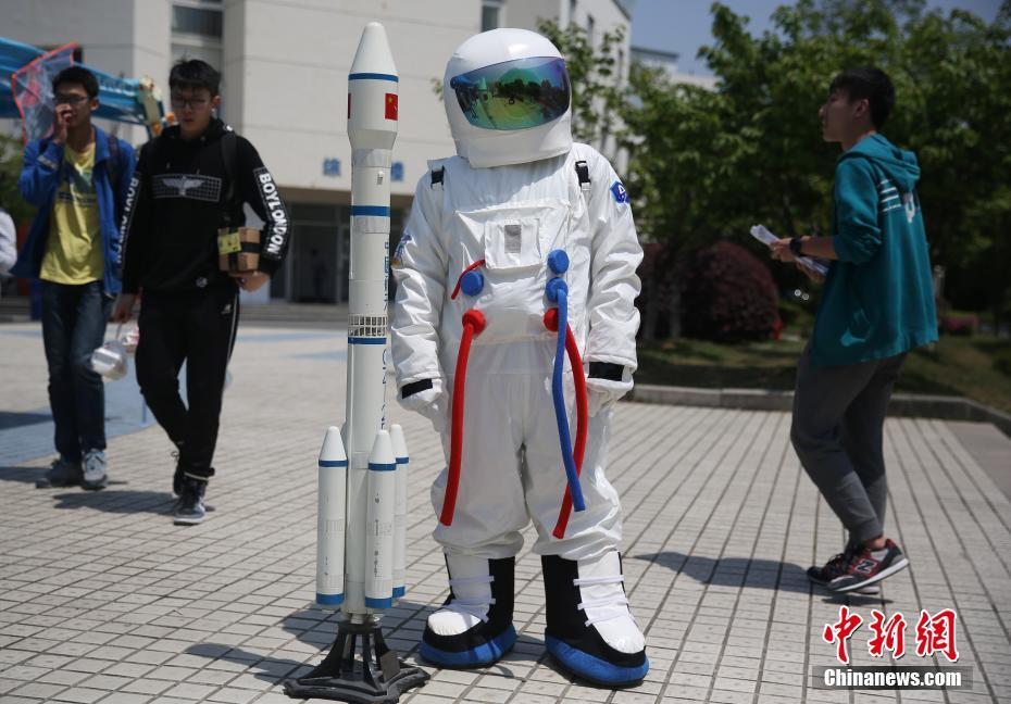 Student with a space suit and model Long March 2F at Nanjing University of Aeronautics and Astronautics on April 24, 2017.