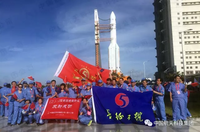 Rocket team members pose as the Long March 5 rolls out (CASC).