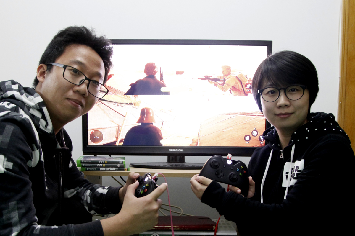 Luo Rangfeng (L) with his wife Rong Zhihui playing the new Star Wars video game Battlefront.