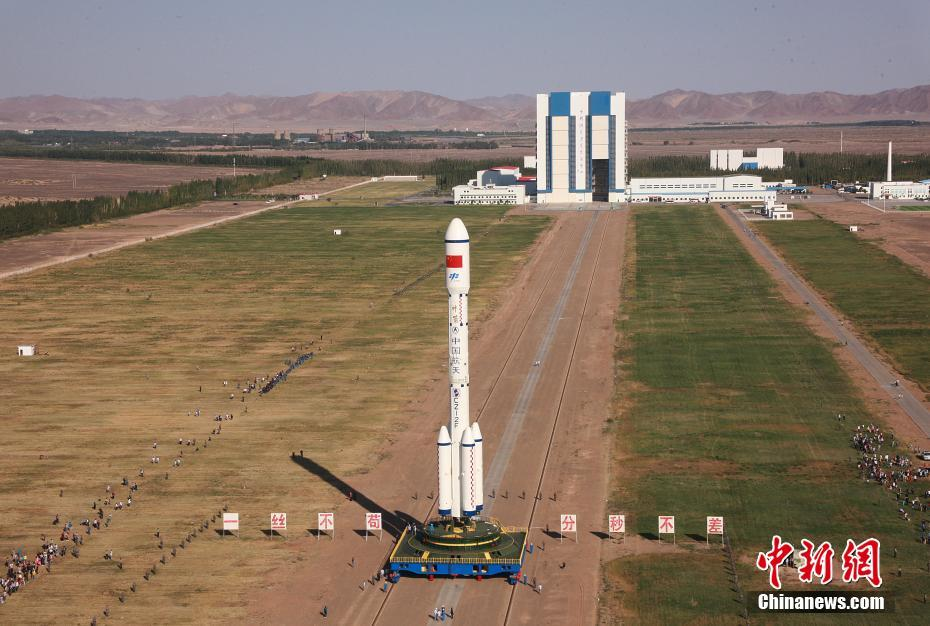 Tiangong-2 and its carrier rocket heading from testing building (background) to the launch tower at Jiuquan.