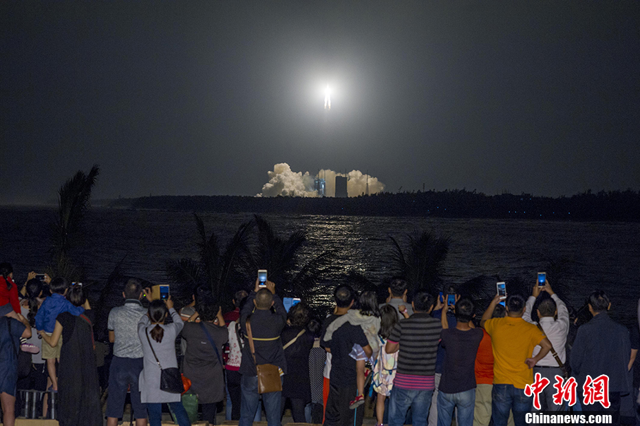 Spectators watch and film the first launch of China's Long March 5 rocket at Wenchang on November 3, 2016.
