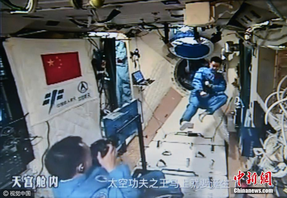 Shenzhou-11 astronauts Jing and Chen recording a science lesson aboard Tiangong-2.