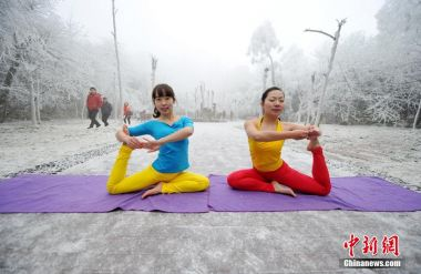 Women practice yoga in snow