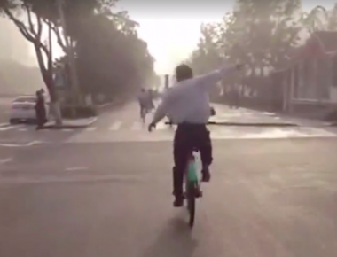 Elderly Chinese man practices Tai Chi on bicycle