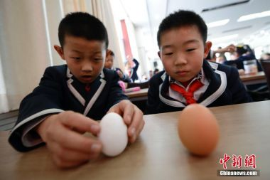 Chinese students celebrate spring equinox by erecting eggs